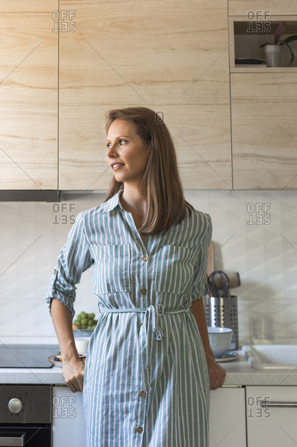 Portrait of beautiful Caucasian woman standing at her kitchen.
