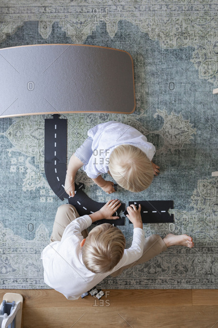 Form above photo of toddler boys playing with toy car track at home.