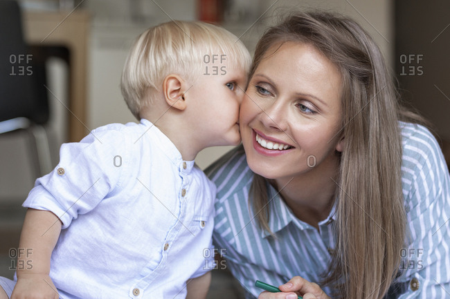 Cute toddler boy kissing his smiling beautiful mother.