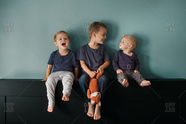 Three little boys sitting together in front of a blue wall