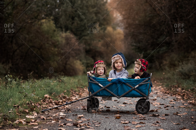 Three boys in a blue wagon on rural path in autumn