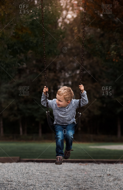 Blonde toddler boy on swing at a park