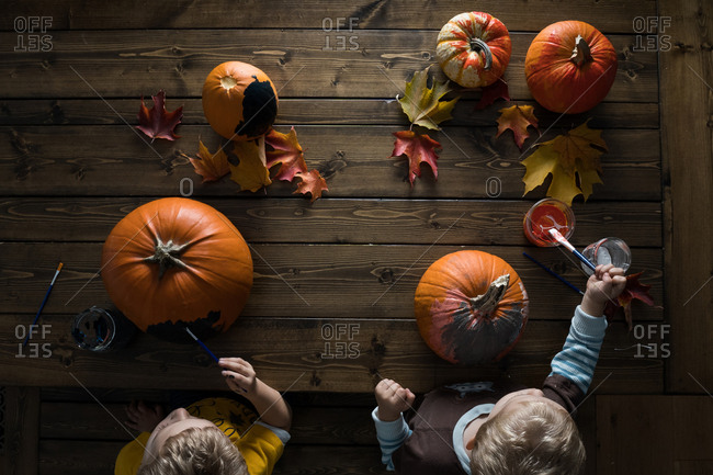Overhead view of two boys painting pumpkins