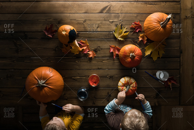 Overhead view of two little boys painting pumpkins