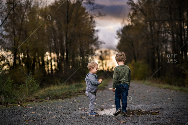 Rear view of two little boys walking on dirt path with puddles at sunset