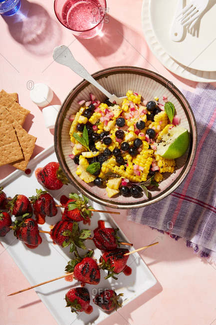 Colorful fruit and veggie dish beside grilled strawberries