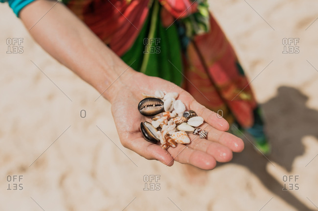 A woman's holding seashells found on a beach in Bali