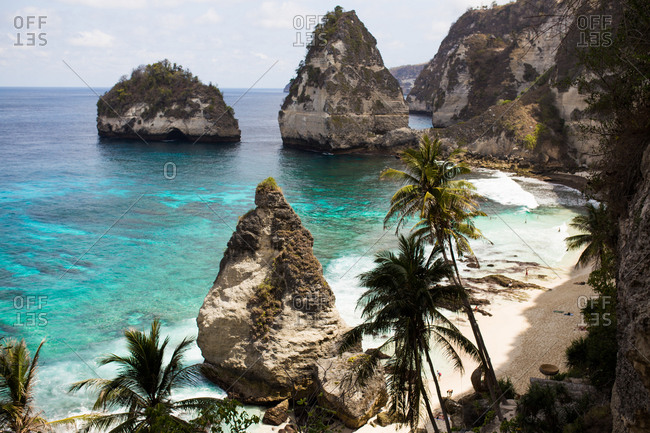 Beautiful view of palm trees and rock formations on a beach in Bali