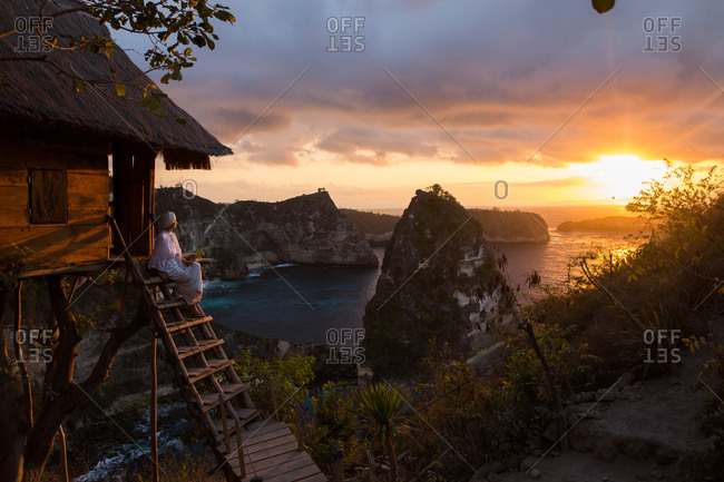Woman taking in the sunrise on stairs to hut on the coast of Bali