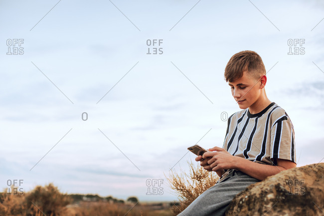 Teenage boy using cell phone while sitting in a field at sunset
