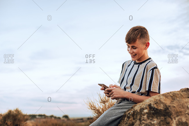Teenage boy using cell phone and laughing while sitting in a field at sunset