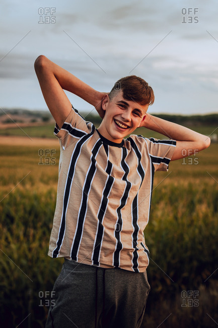 A smiling teenage boy in the wild during sunset with his hands behind his head