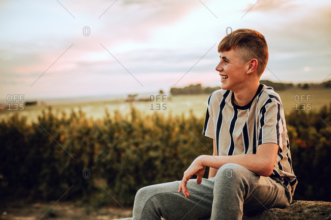 Portrait of an adolescent boy in the wild during sunset