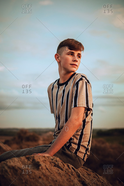 An adolescent boy sitting on rock in the wild during sunset