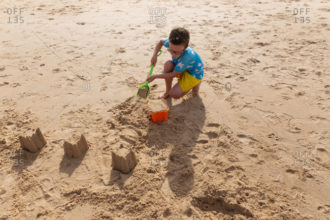 A boy digging in the sand while building a sandcastle on a beach