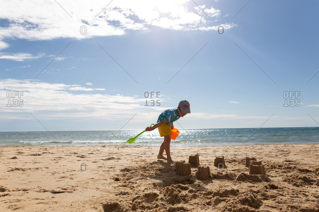 Young boy building a sandcastle on a beach
