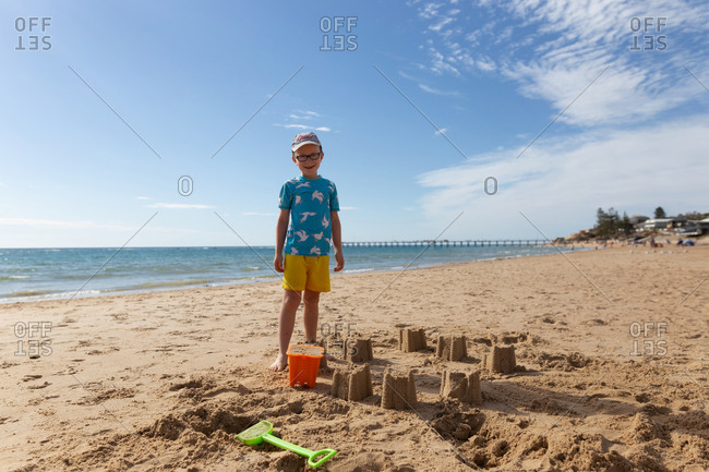 Happy boy standing by his sand creation on a beach