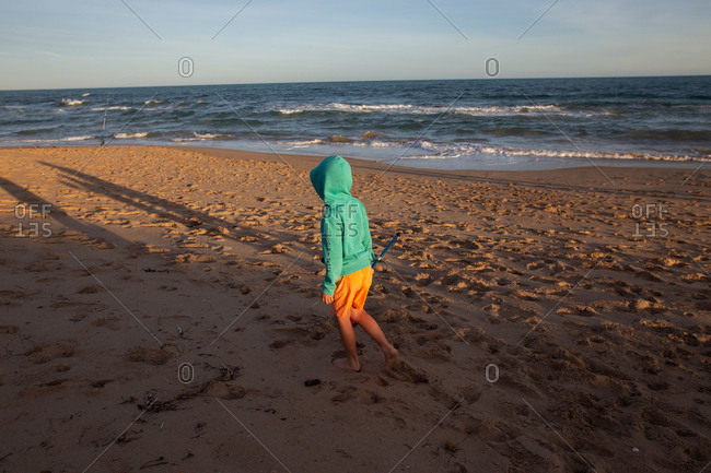 Young boy walking on a beach at sunset