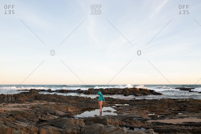 Boy playing in tide pool on a beach at sunset