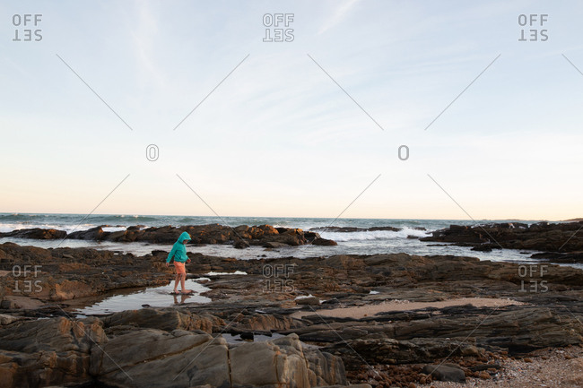 Boy walking in tide pool on a beach at sunset