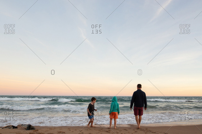 Two boys looking out at the ocean waves at sunset with their dad