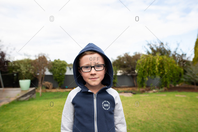 Portrait of a little boy wearing glasses and a hoodie outdoors
