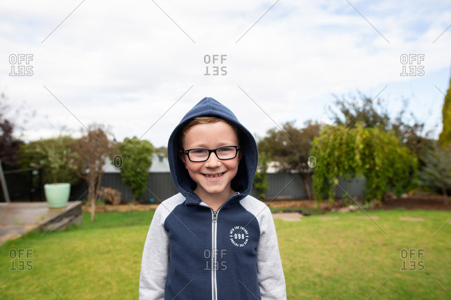 Portrait of a smiling little boy wearing glasses and a hoodie outdoors