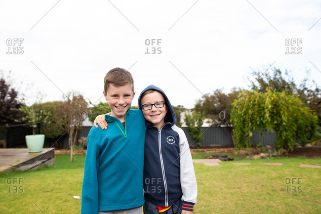 Two boys standing with arms around each other outdoors