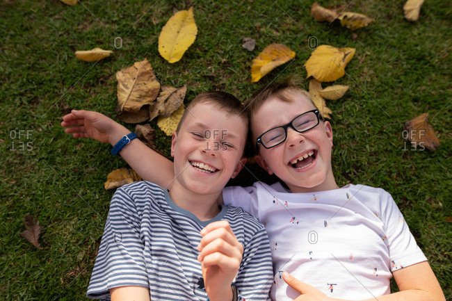 Overhead view of two boys lying on ground with leaves