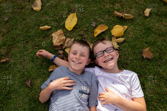 Two boys lying on ground with leaves laughing