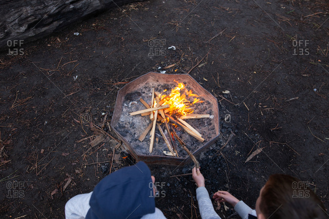 Overhead view of two boys putting sticks in a campfire