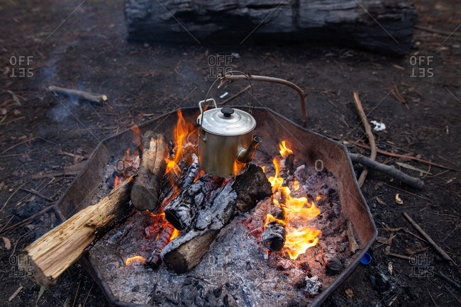 Metal tea kettle heating up over a campfire
