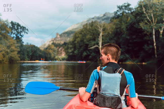 Back view of sportswoman sitting in red canoe and raising paddle on Sella river decline in Spain