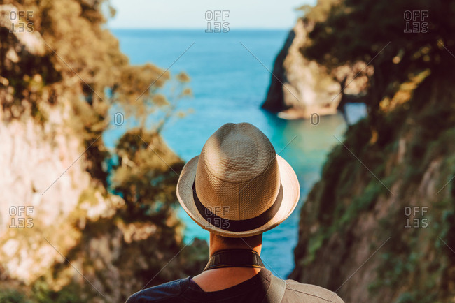 Back view of woman in hat standing by wooden railing and enjoying breathtaking view of sea and cliffs in Ribadedeva Asturias Spain