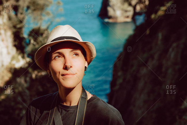 Young woman in hat standing with camera hanging on neck and enjoying picturesque view of sea and rocks in Ribadedeva Asturias Spain