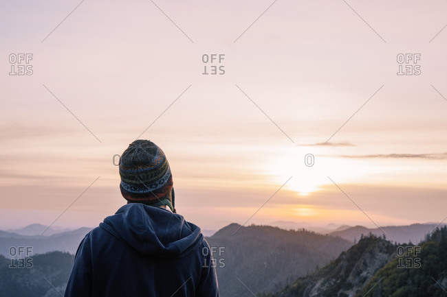 Back view of touristic person in mountains enjoying serene view of sunrise in USA