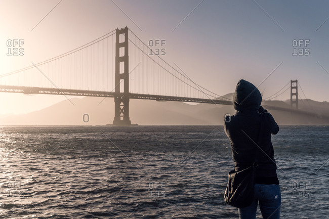 Back view of person in jacket with hood looking at long bridge under endless wavy sea in USA