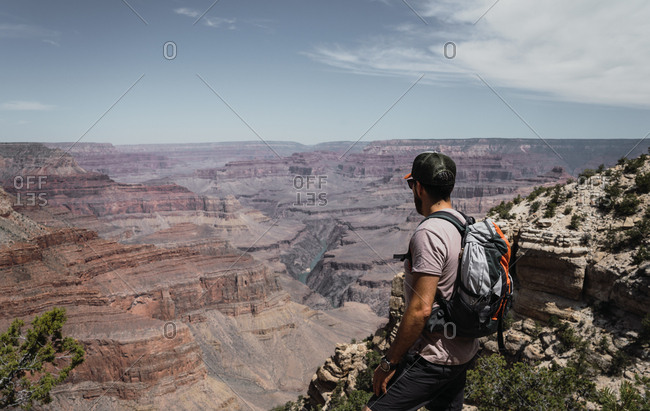 Side view of man with backpack contemplating and standing on mountain top on hot summer day in USA