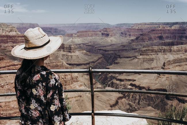 Tourist gazing while standing on edge of picturesque canyon