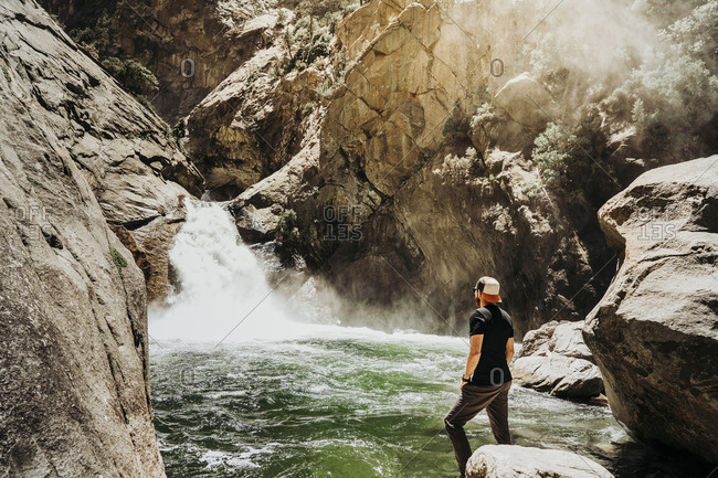 Side view of man in casual clothes contemplating water cascade surrounded with rocky slopes and mist on sunny day in USA