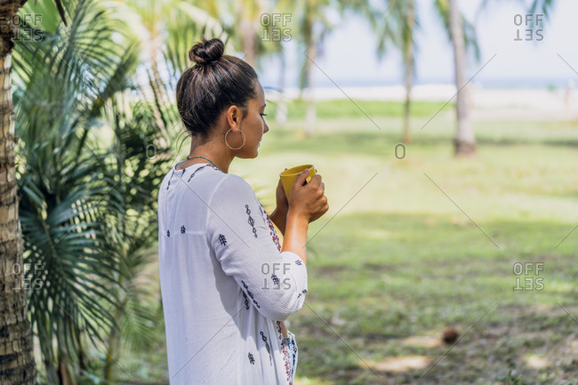 Side view peaceful woman drinking coffee from mug and standing by palm tree on sunny seaside in Costa Rica