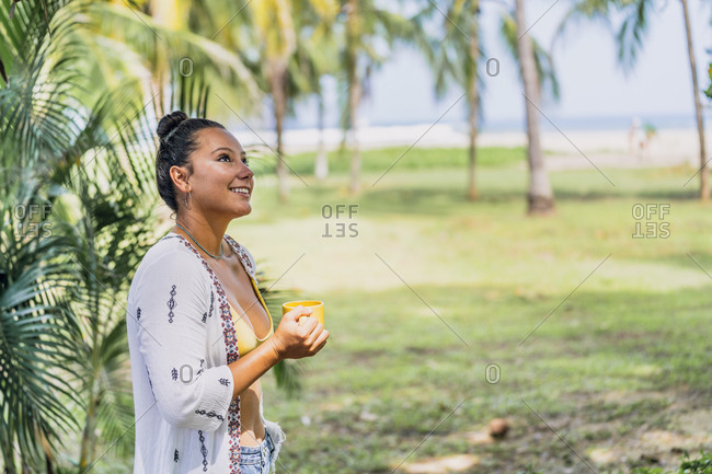 Side view peaceful woman drinking coffee from mug and standing by palm tree looking up on sunny seaside in Costa Rica