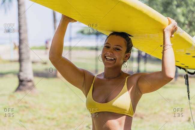 Positive fit woman in swimsuit carrying yellow paddleboard over the head in sunny seashore by palm trees in Costa Rica