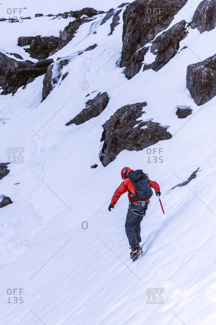 Unrecognizable person with backpack and hiking equipment walking in a slope in daylight