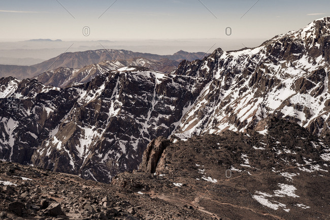 Tranquil rocky slopes of mountain chain with snowy peaks in daylight