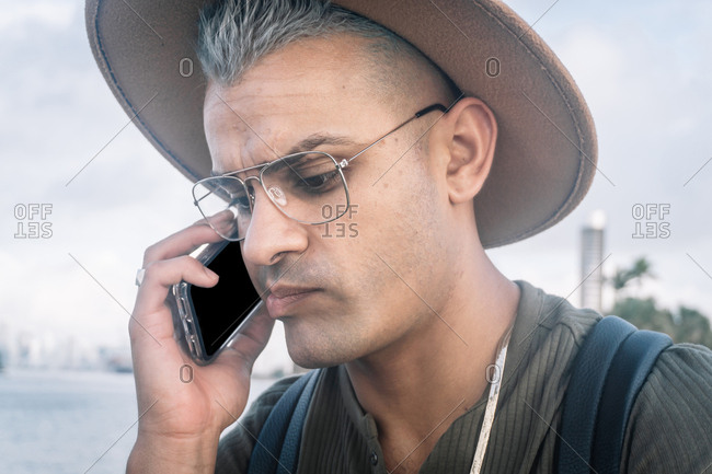 young man with a hat and talking on cellphone with worried expression. Portrait