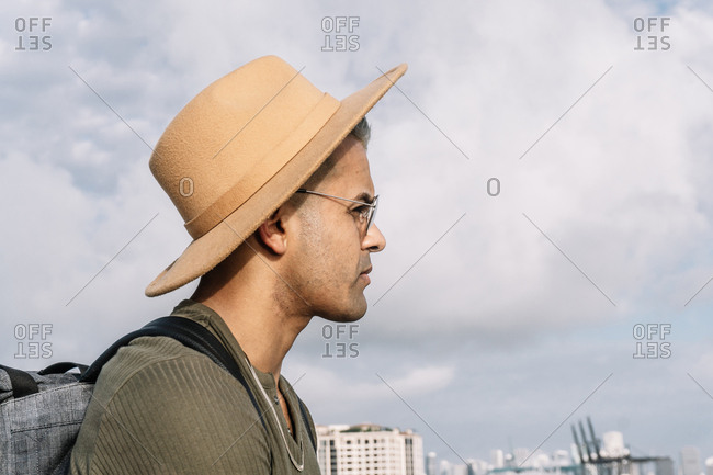 Side view of a man with a nice hat and glasses looking straight ahead. Destinations and travel concept