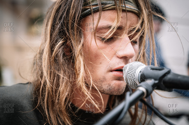 Close-up portrait of expressive street singer man with long hair singing in the street