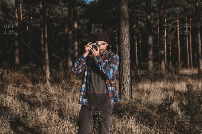 Bearded man in casual outfit taking photo with camera while standing surrounded with evergreen trees and dried grass on cold sunny day