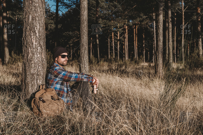 Side view of man in hat and sunglasses leaning on evergreen tree and sitting on grass by backpack on sunny day